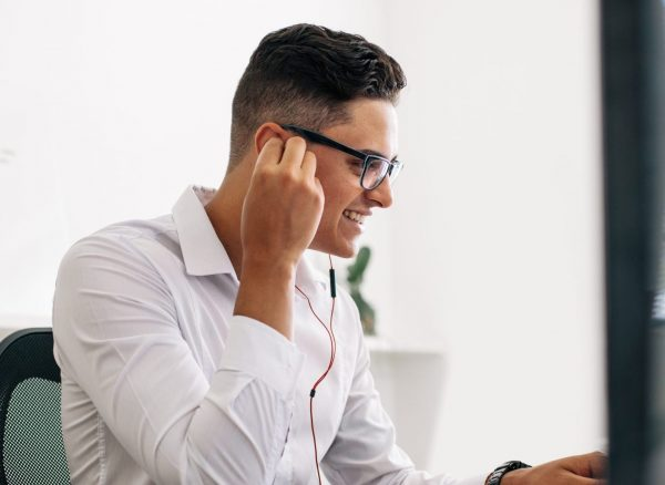 Smiling software developer sitting at his office desk working on laptop wearing earphones. Man wearing spectacles working on laptop computer in office.
