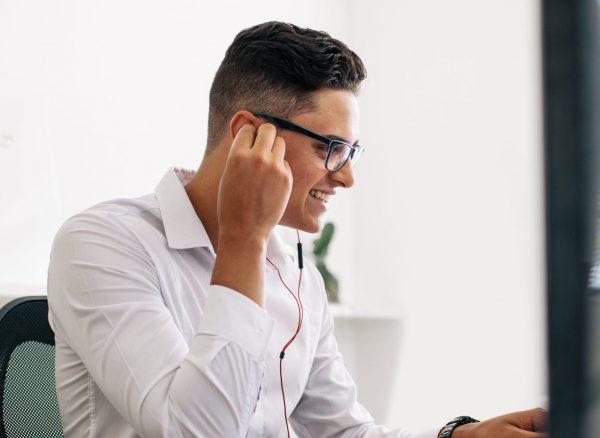 Smiling software developer sitting at his office desk working on laptop wearing earphones. Man wearing spectacles working on laptop computer in office.